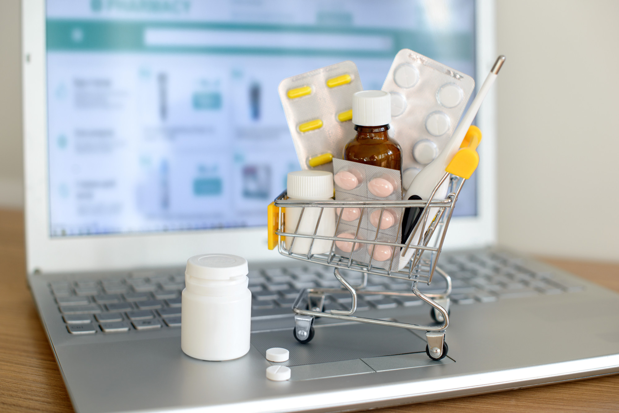 Shopping cart toy with medicines in front of laptop screen with pharmacy web site on it. Pills, blister packs, medical bottles, thermometer set. Health care and buying medications online.