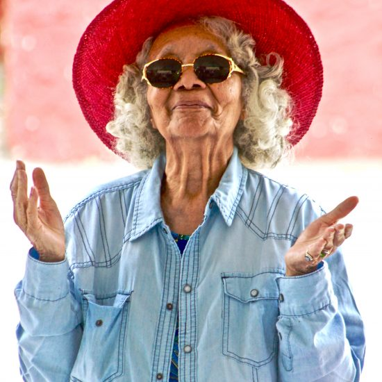 Elderly woman with red sun hat, looking slightly confused. Many people are similarly confused about Myrbetriq, a treatment option for overactive bladder.