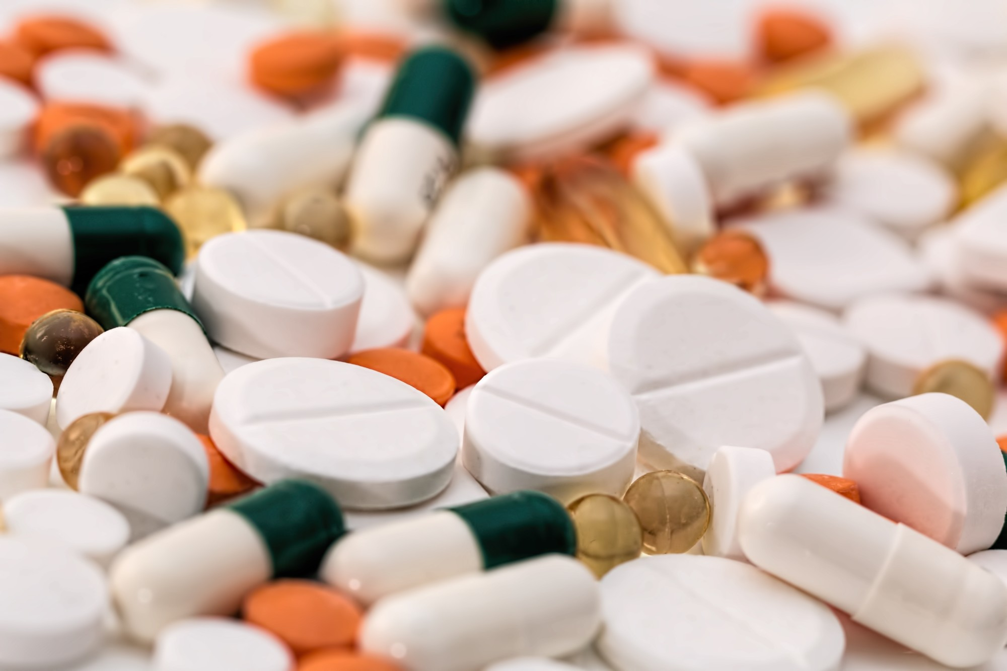 A variety of pills of different colours all together on a table, indicating that many prescription medications can be bought online, making getting your pills easier than every before.