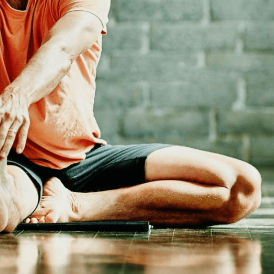 Man seated on floor stretched out right leg to exercise and strengthen ahead of knee surgery