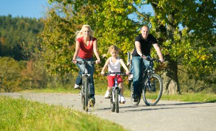 A Family cycling together outdoors.