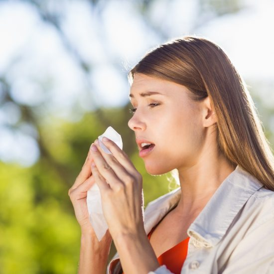 A woman with pollen allergies, sneezing into a tissue.