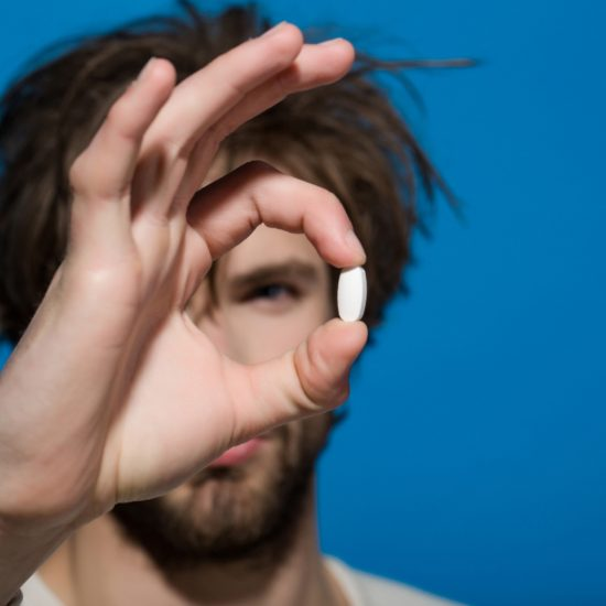 Man holding a white pill in his hand. Pill is in focus against a bright blue background, showing the importance of Zoloft for people with depression.